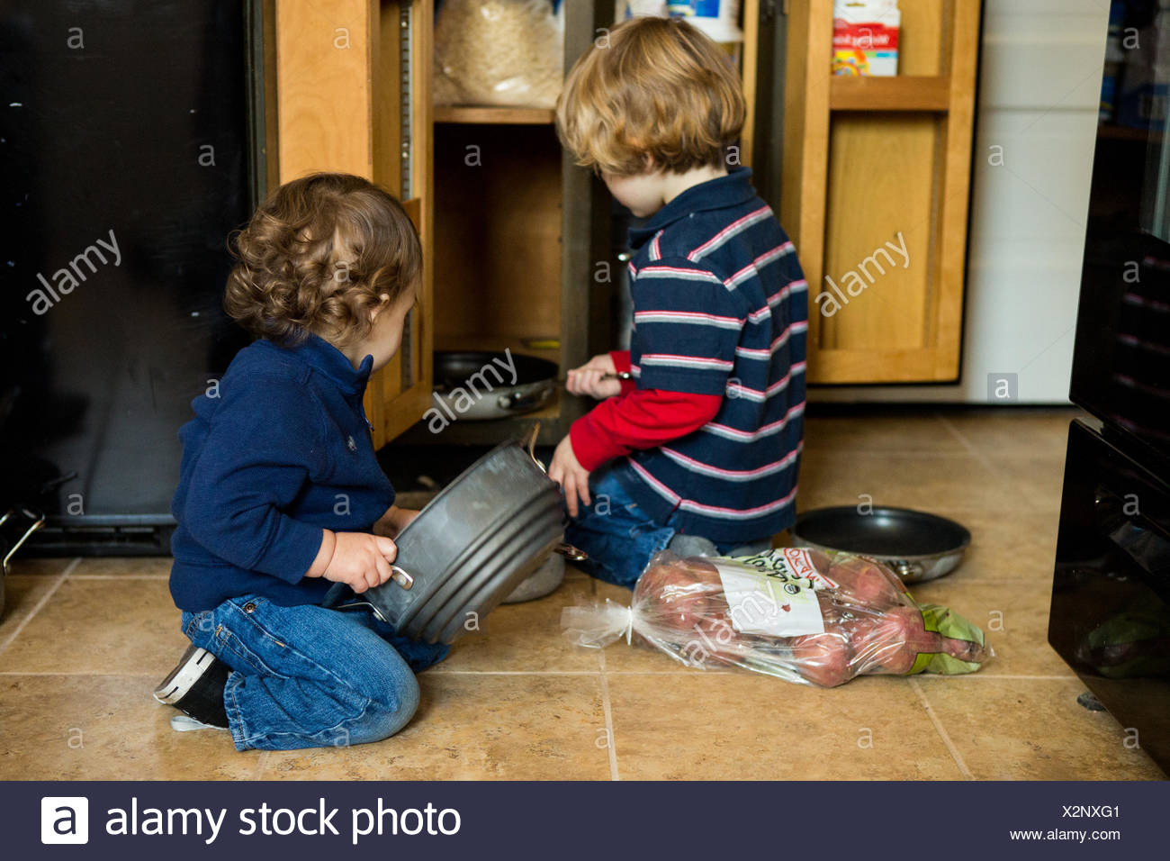 Two boys emptying a kitchen cabinet - Stock Image