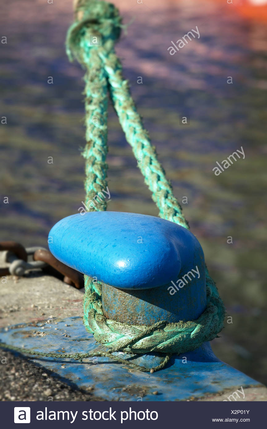 Close-up of a hawser tied to a blue bollard - Stock Image