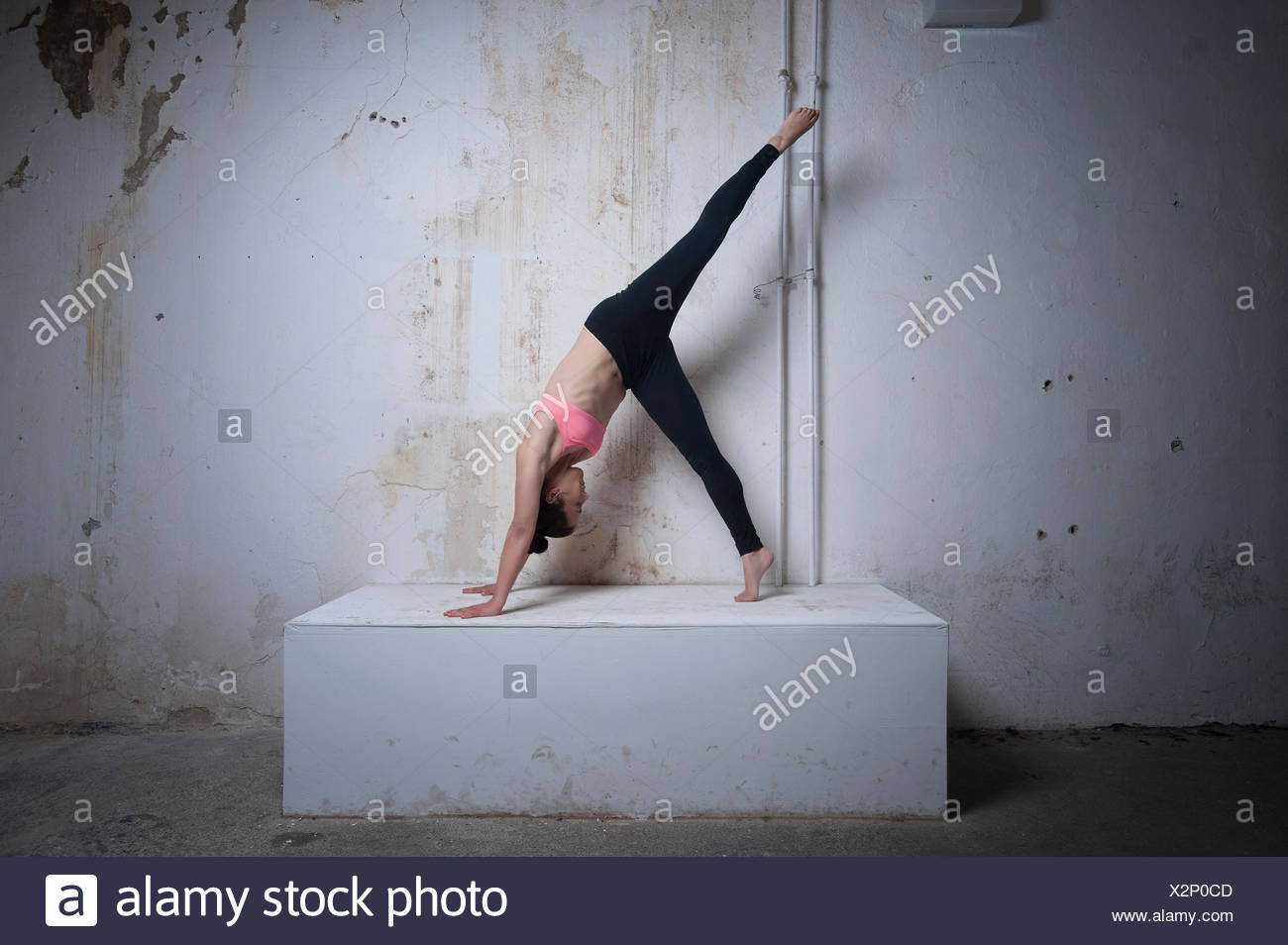 Mid adult woman practicing one legged downward facing dog position on concrete block, Munich, Bavaria, Germany - Stock Image