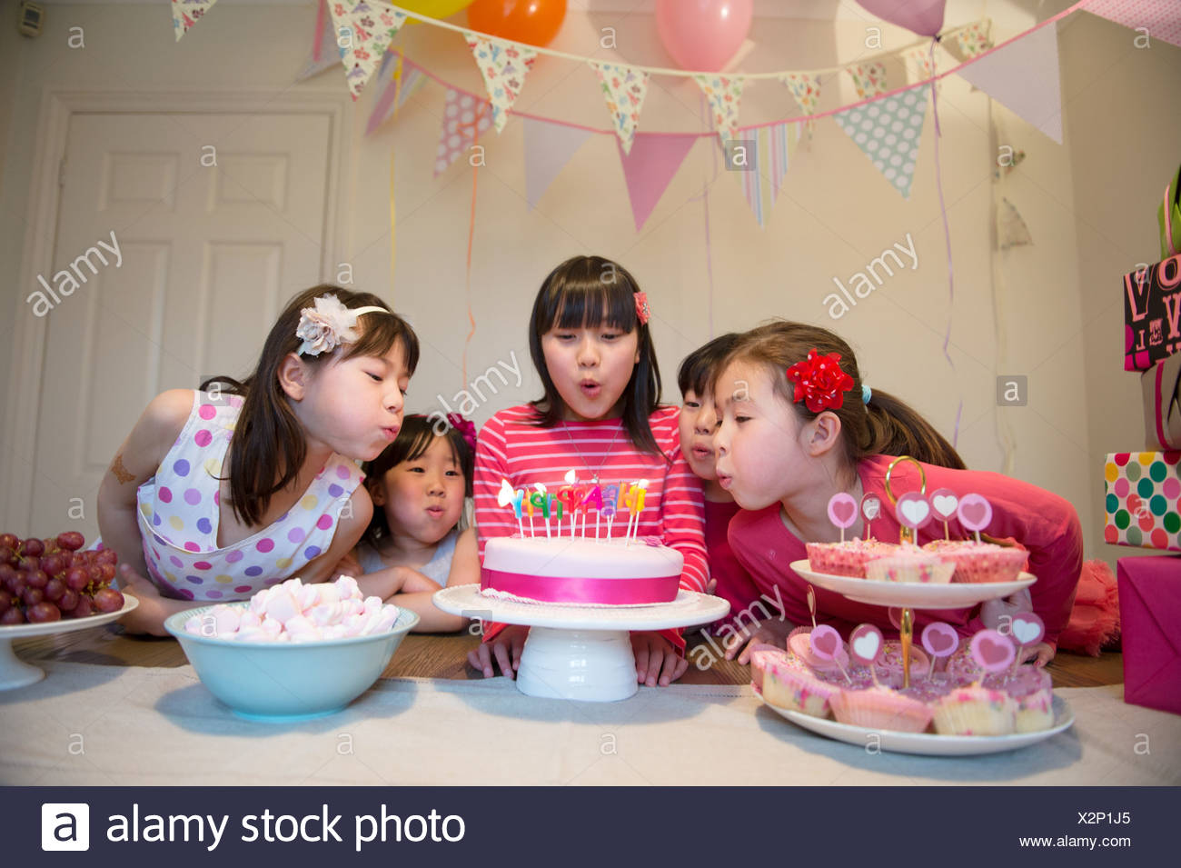 Girls blowing out birthday candles on cake - Stock Image