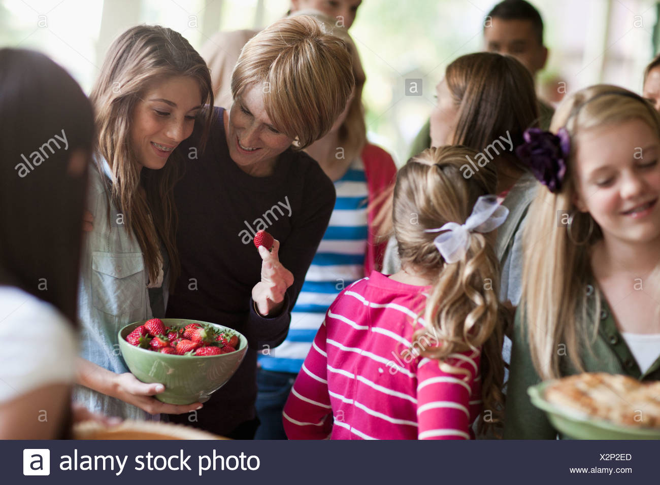 Girls (10-11, 14-15) with family during celebration event - Stock Image