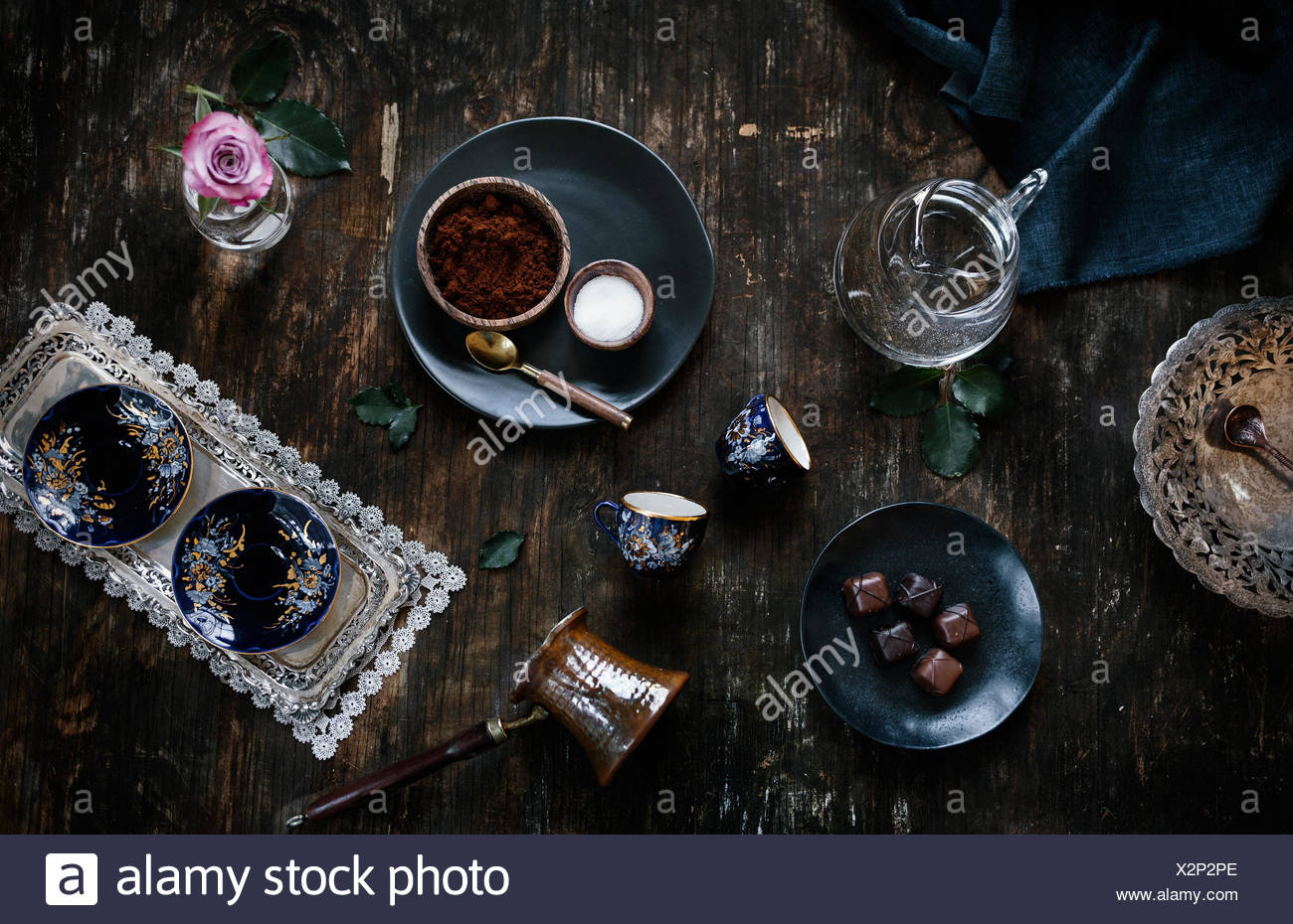 Ingredients for Turkish Coffee (coffee, sugar, water), coffee cups and traditional coffee pot are displayed on a reclaimed wood - Stock Image