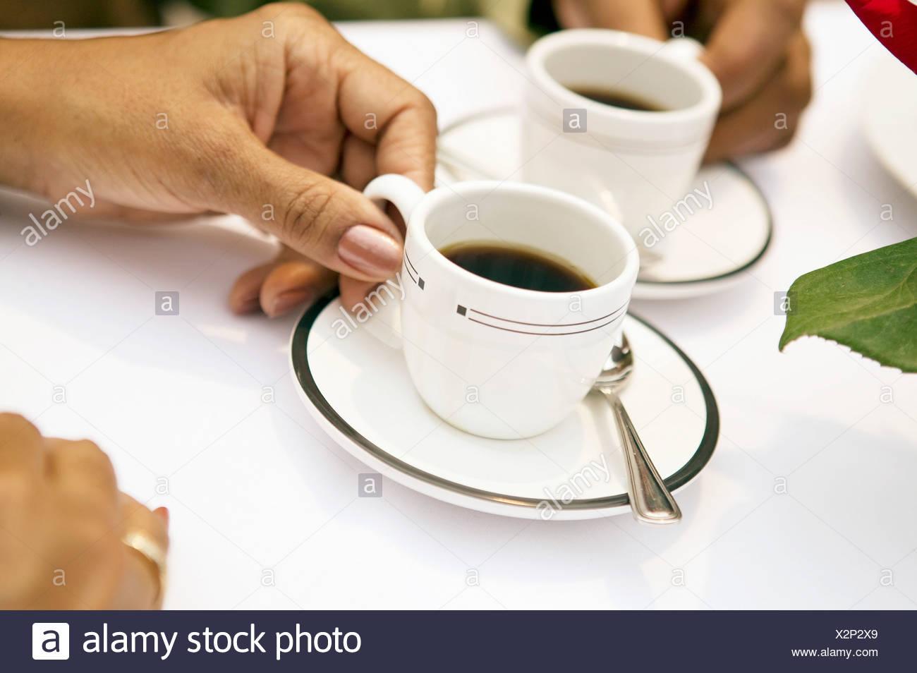 African woman holding espresso mug - Stock Image