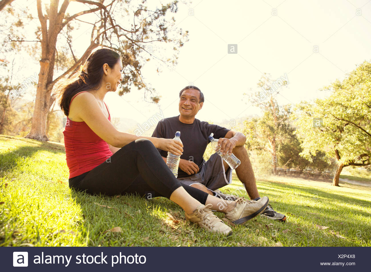 Mature running couple taking a break and drinking water in park - Stock Image
