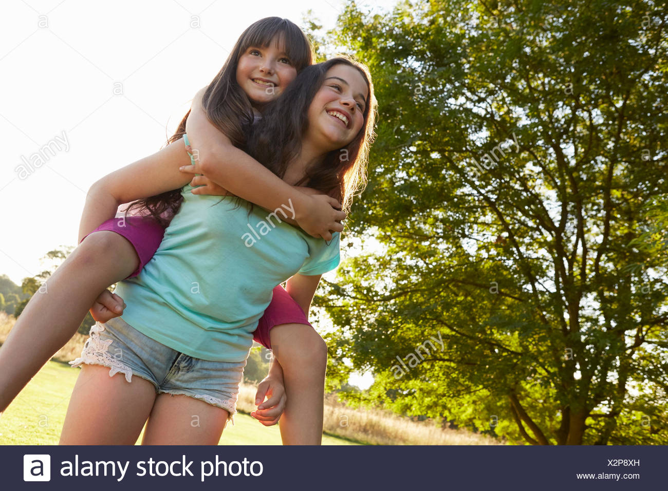 Girl giving her best friend a piggy back in park - Stock Image