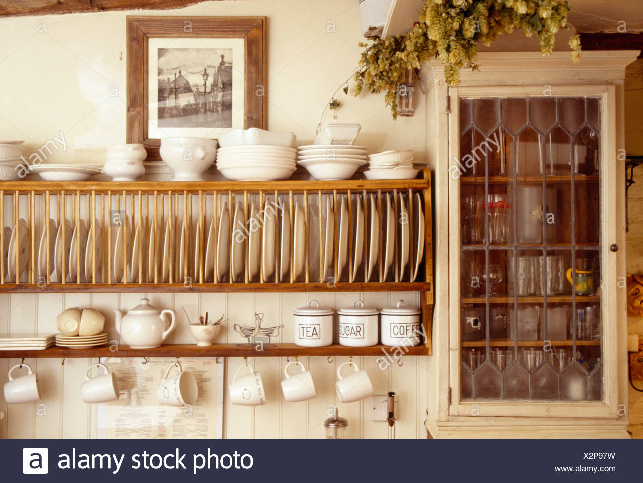 Close-up of cream bowls on wooden plate rack beside small wall cupboard in cottage & Interiors Traditional Kitchens Plate Racks Stock Photos u0026 Interiors ...