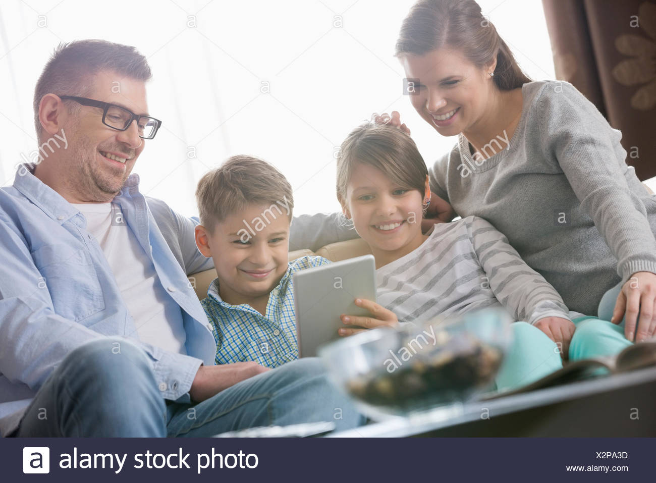 Happy family using digital tablet together in living room - Stock Image