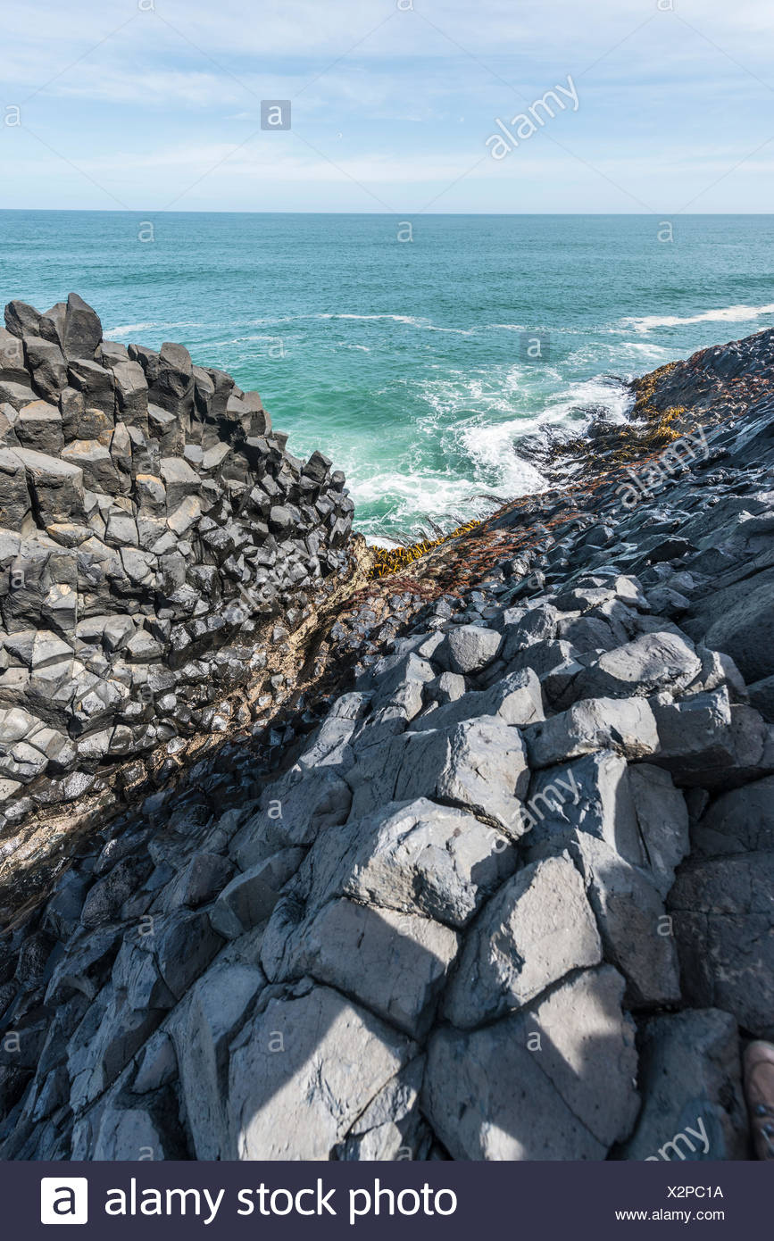 Hexagonal basalt column by the sea, Blackhead, Dunedin, Otago, South Island, New Zealand - Stock Image