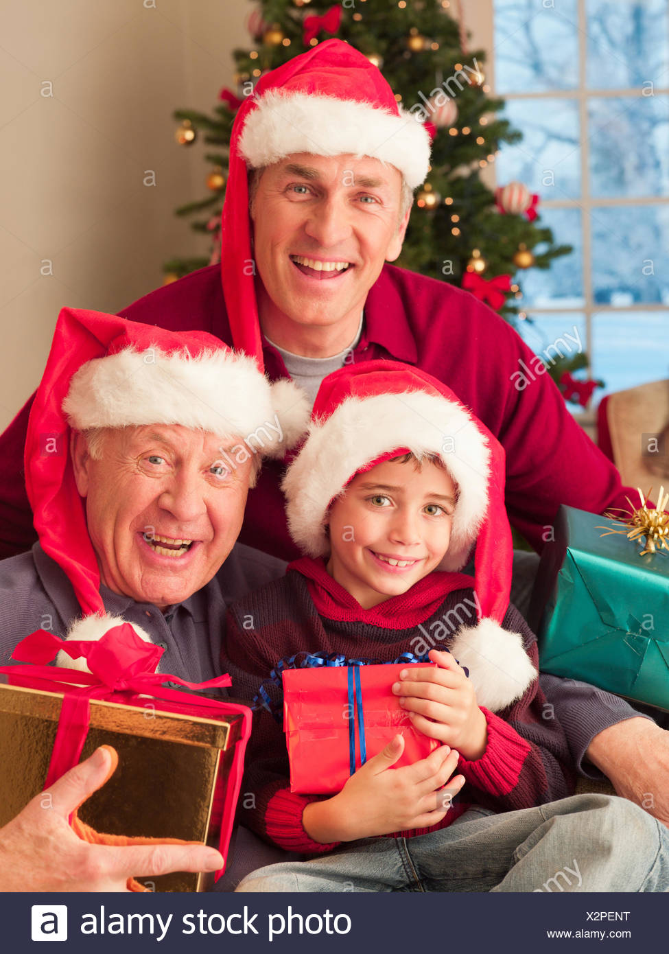 Multi-generation family wearing santa hats and holding Christmas gifts - Stock Image