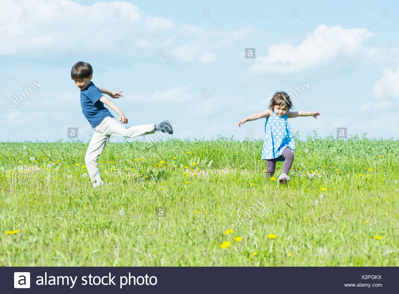 Children running in field with arms out - Stock Image