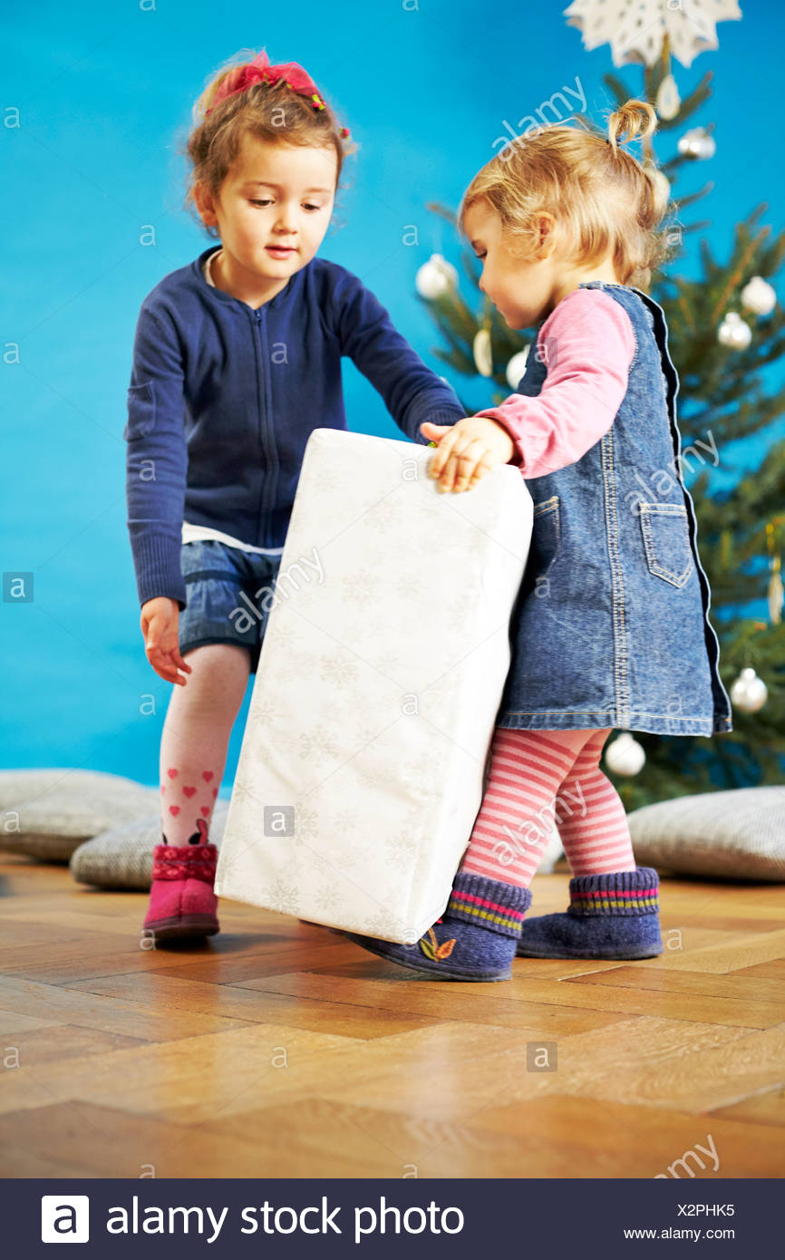 Two girls carrying Christmas present, Munich, Bavaria, Germany - Stock Image
