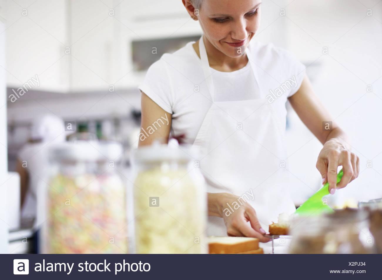 Woman decorating cake - Stock Image