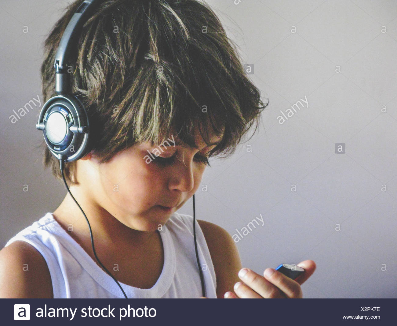 Boy wearing headphones and using mp3 player - Stock Image