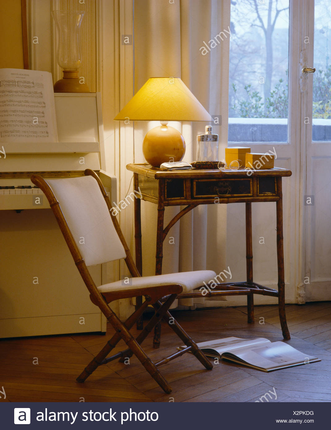Folding Chair With Cream Cushions Beside Antique Table With Lighted Lamp In  Front Of French Windows