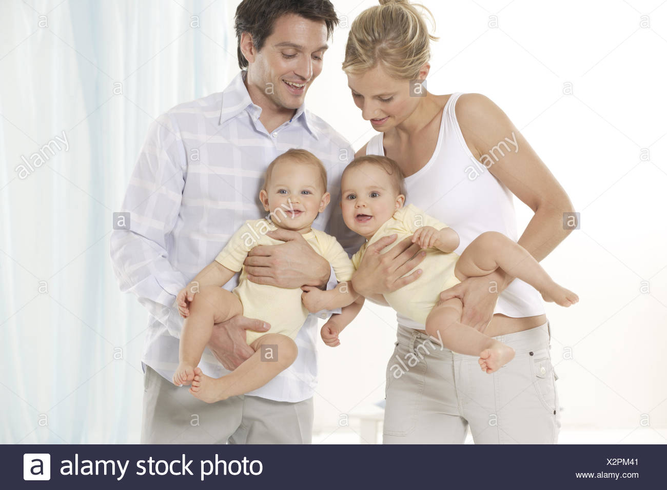 Parents holding twin babies - Stock Image