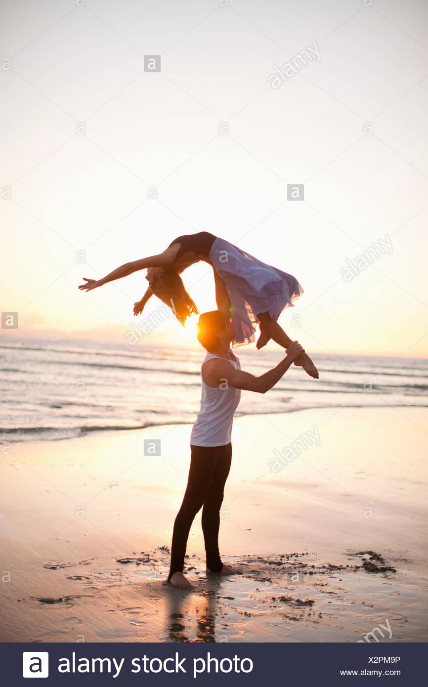 Young man lifting dancing partner on sunlit beach - Stock Image