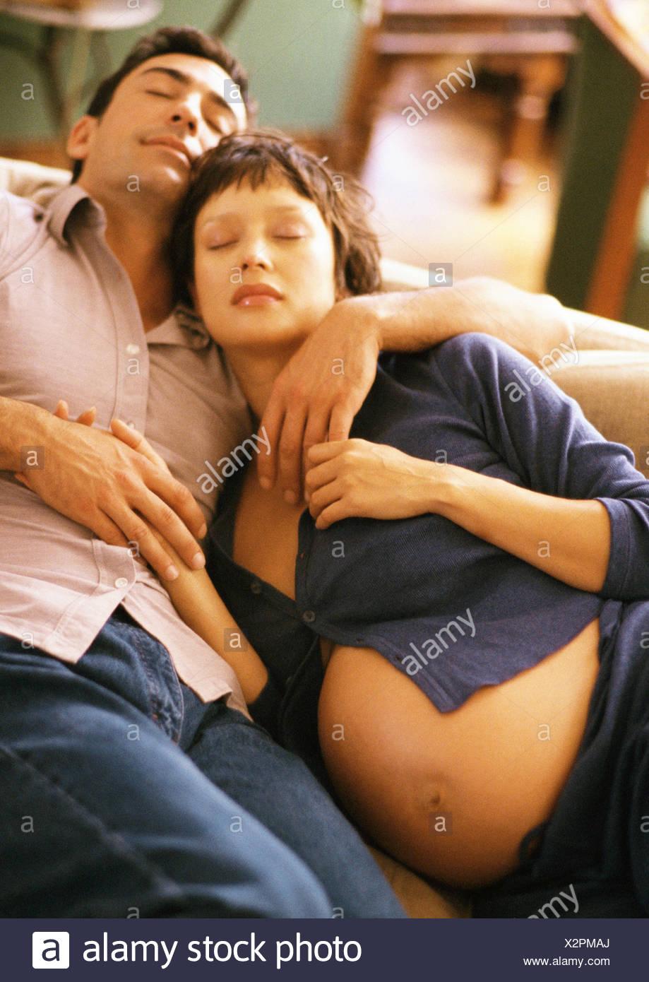 Pregnant woman and man sleeping on sofa - Stock Image