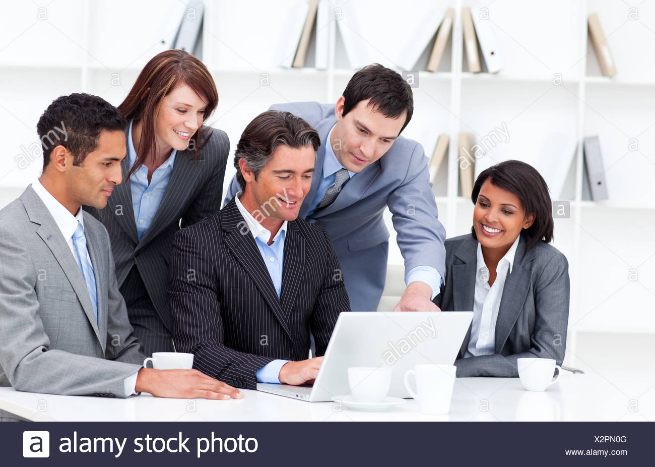 Multi-cultural business team looking at a laptop - Stock Image