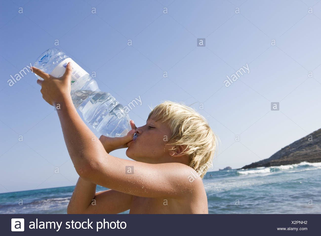 Beach, boy, thirsty, water bottle, drinking, portrait, side view, people, children, blond, summer holidays, holidays, sunny, heat, hot, thirst, drink, bottle, water, sea, mineral water, - Stock Image