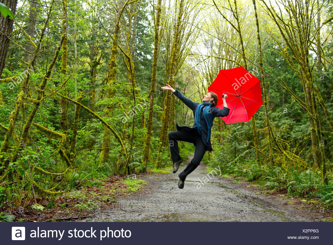 Jumping woman in forest with red umbrella - Stock Image