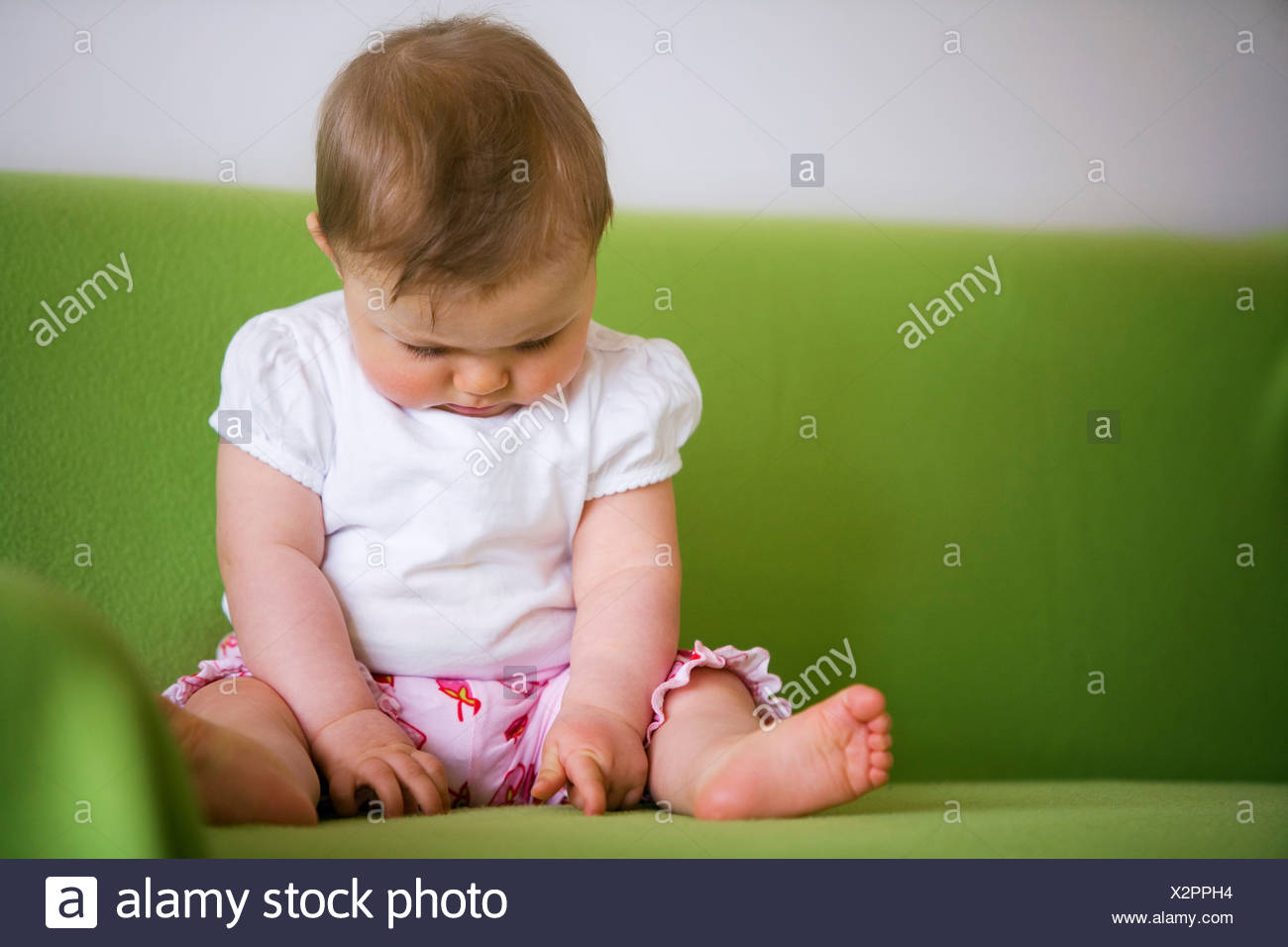 Baby (8 month) sitting on a sofa, Vienna, Austria - Stock Image