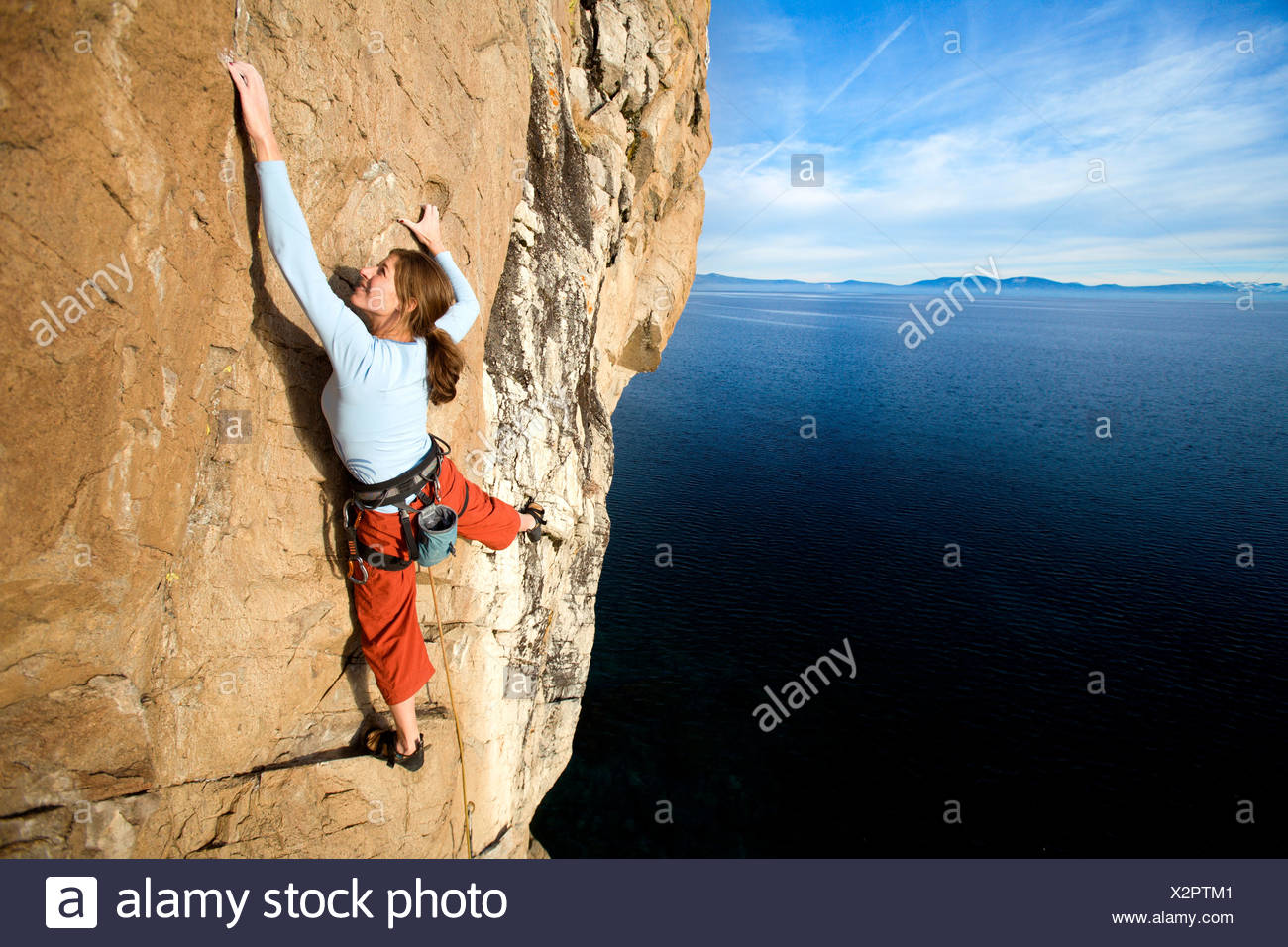 Climber grabs a hold while climbing. - Stock Image