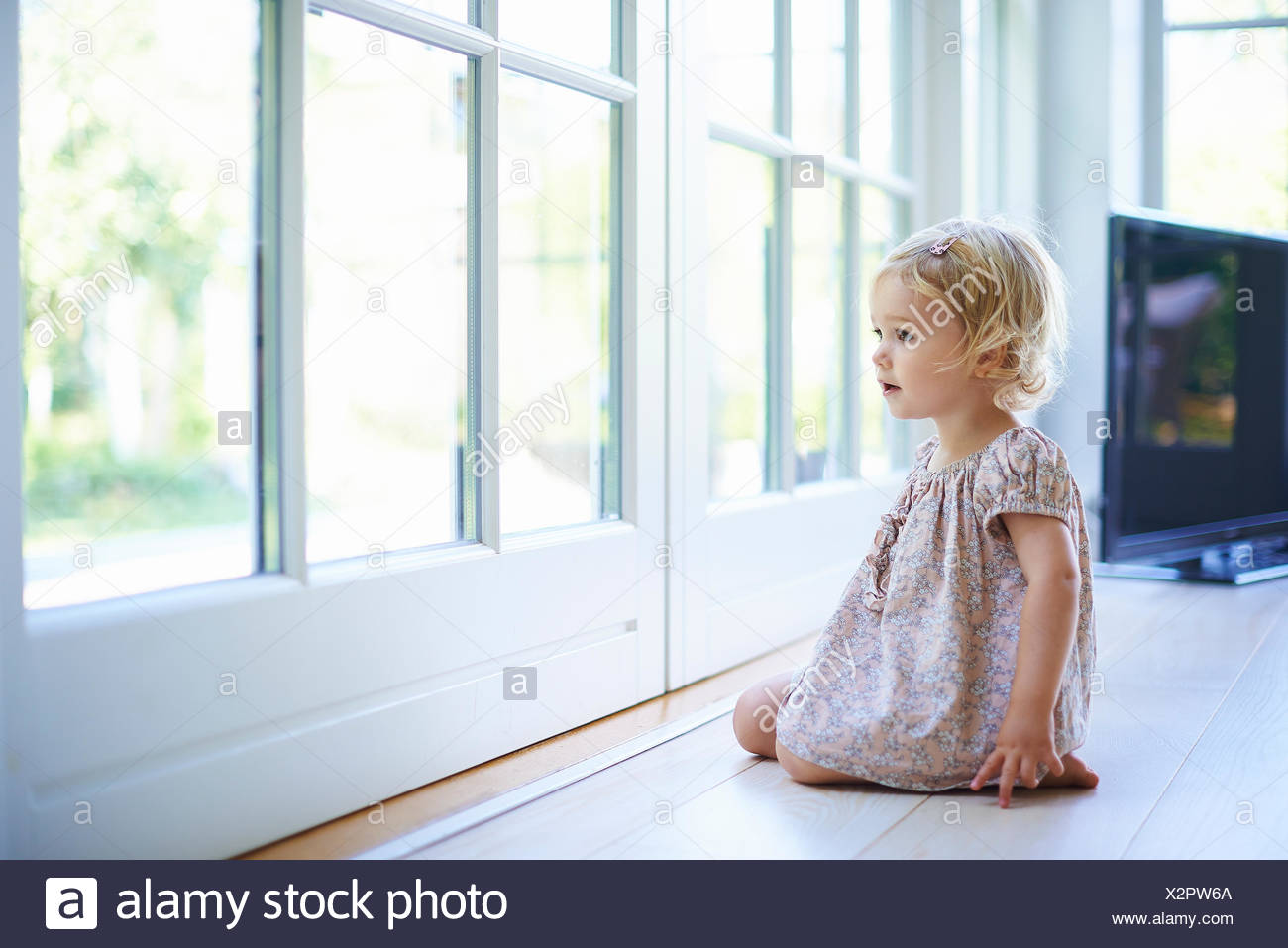 Portrait female toddler sitting on floor looking out of patio doors - Stock Image