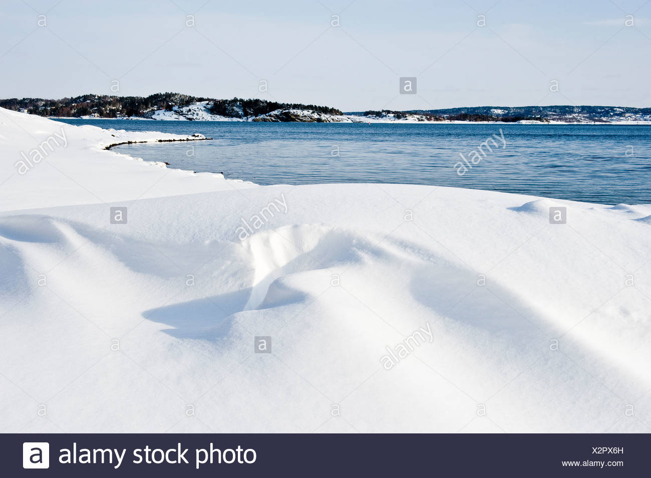 Winter landscape by the water against clear sky - Stock Image
