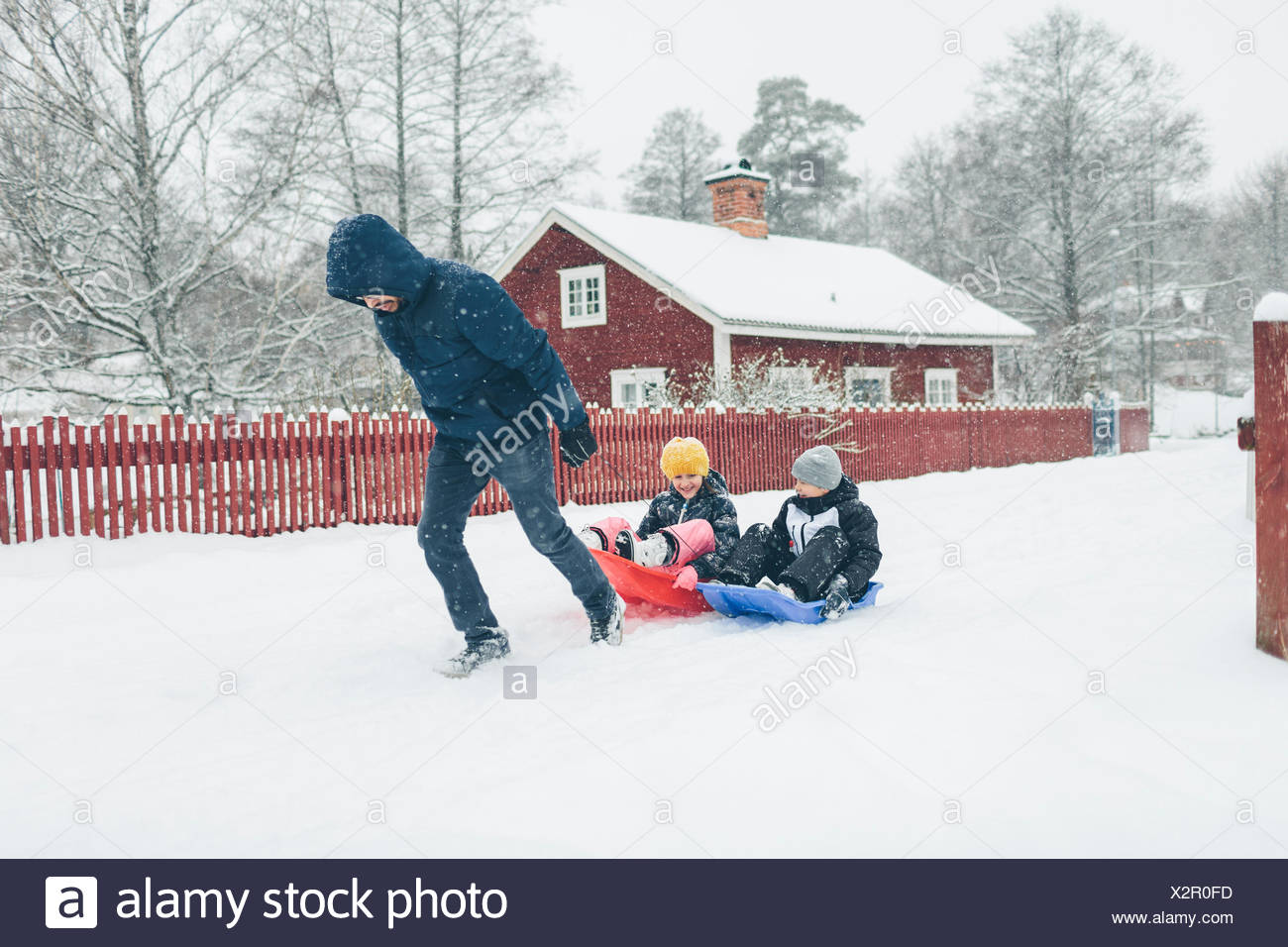 Man pulling children on sled - Stock Image