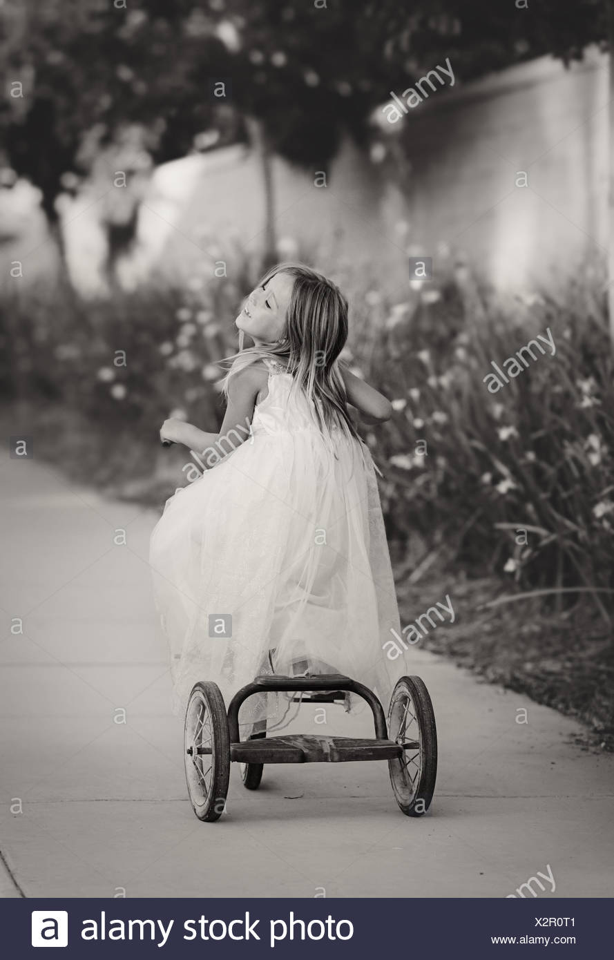 Rear view of a girl on a bicycle - Stock Image