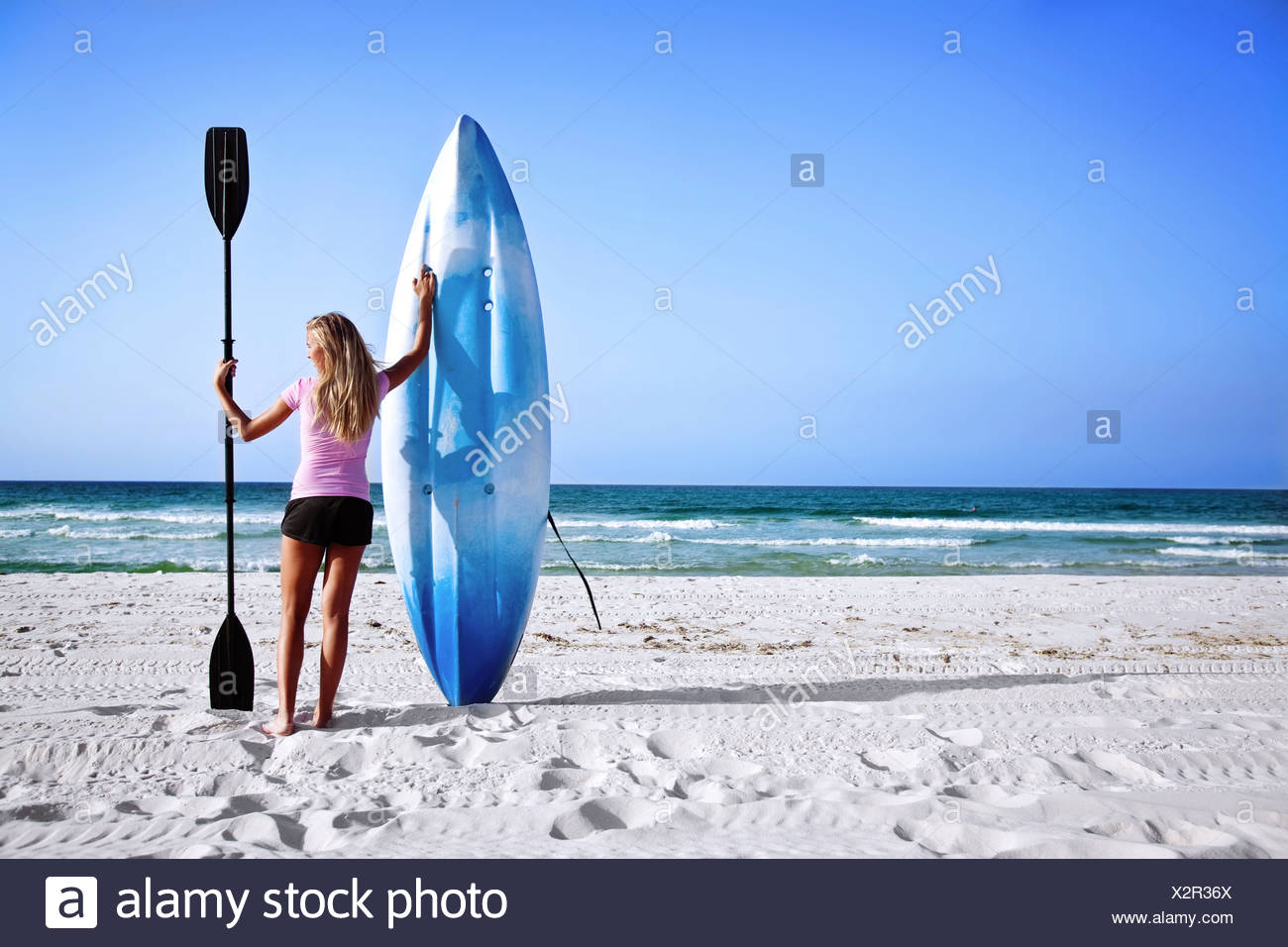 A girl holds up her sea kayak and paddle on Pensacola Beach, Florida. - Stock Image