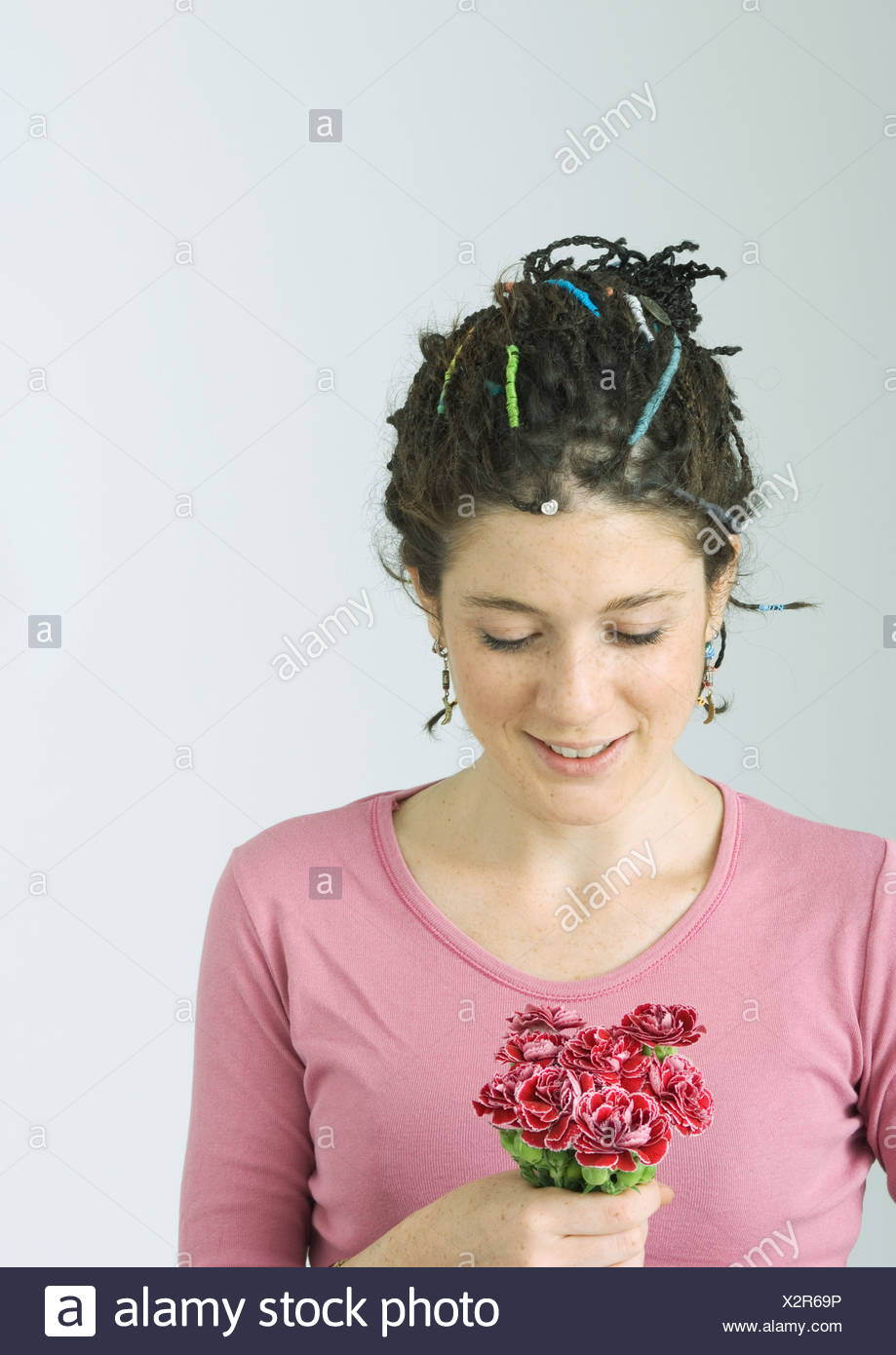 Young woman holding small bouquet of flowers - Stock Image