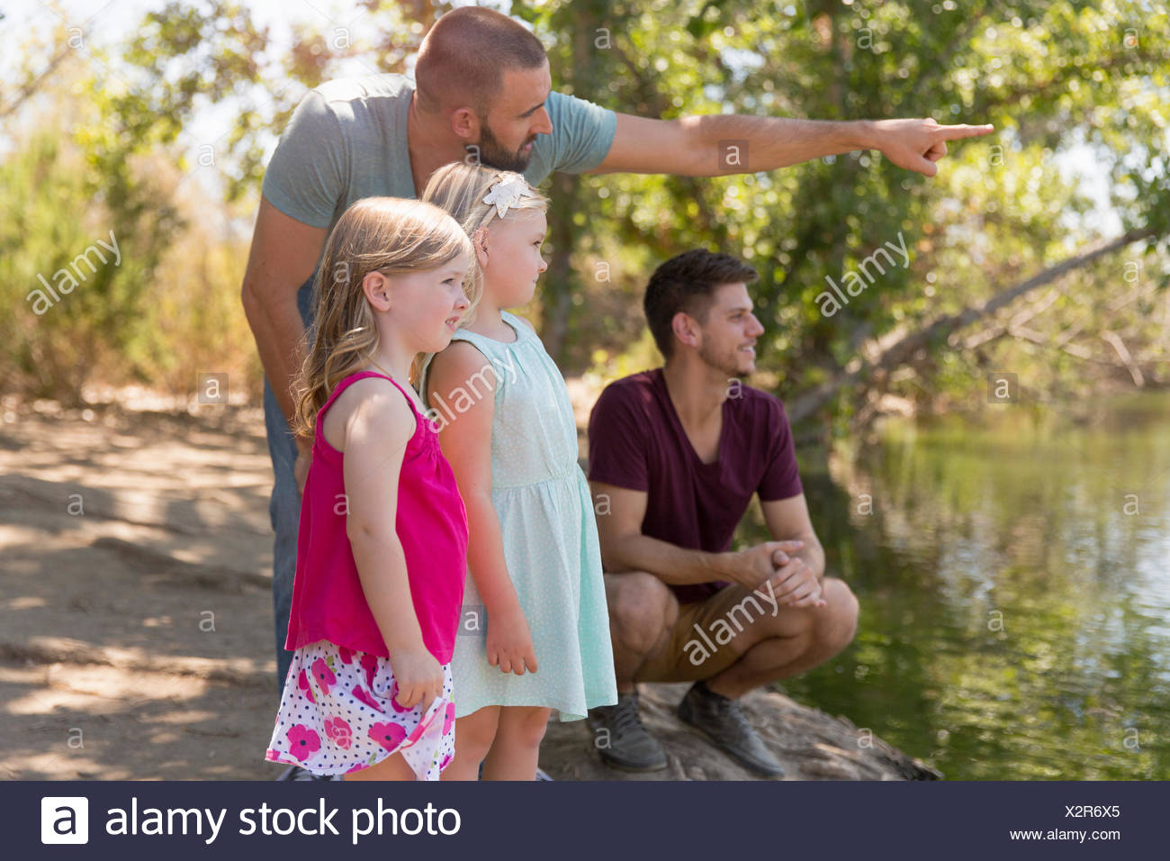 Male couple looking from riverbank with two daughters - Stock Image