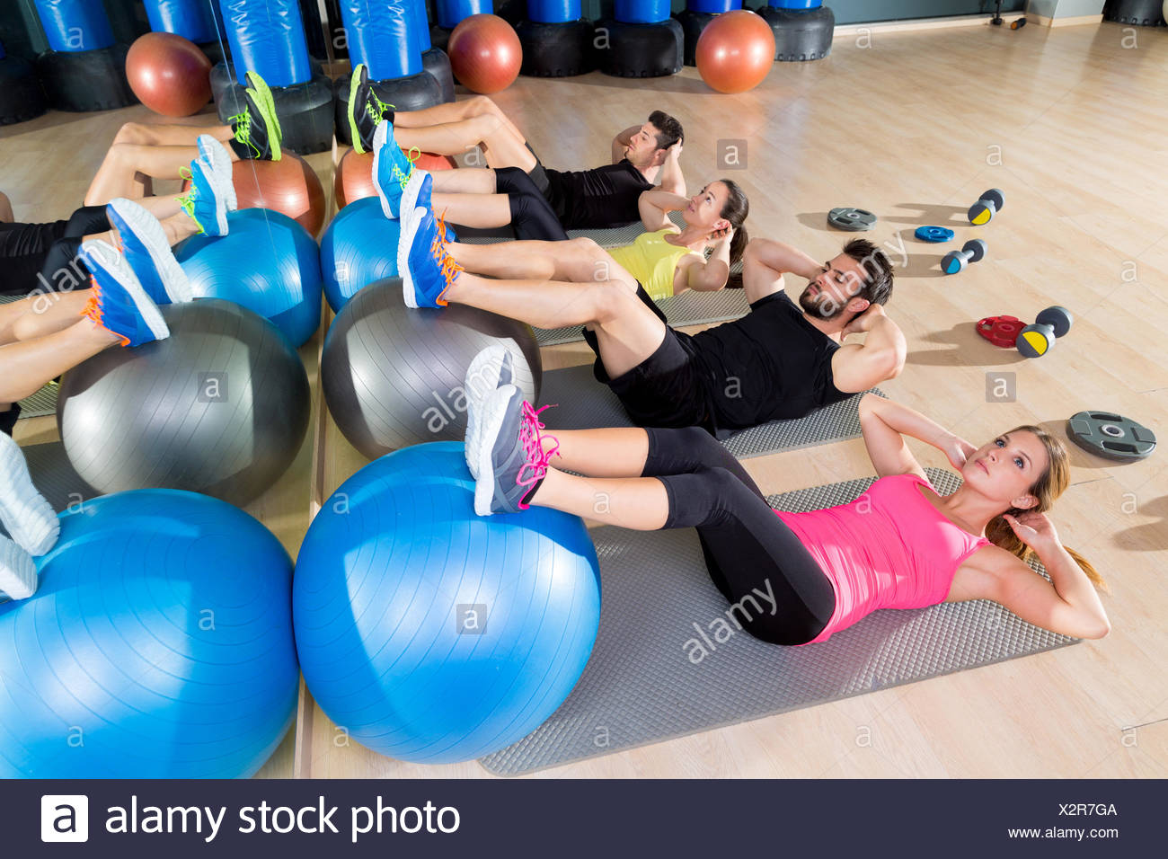Fitball crunch training group core fitness at gym abdominal workout. - Stock Image