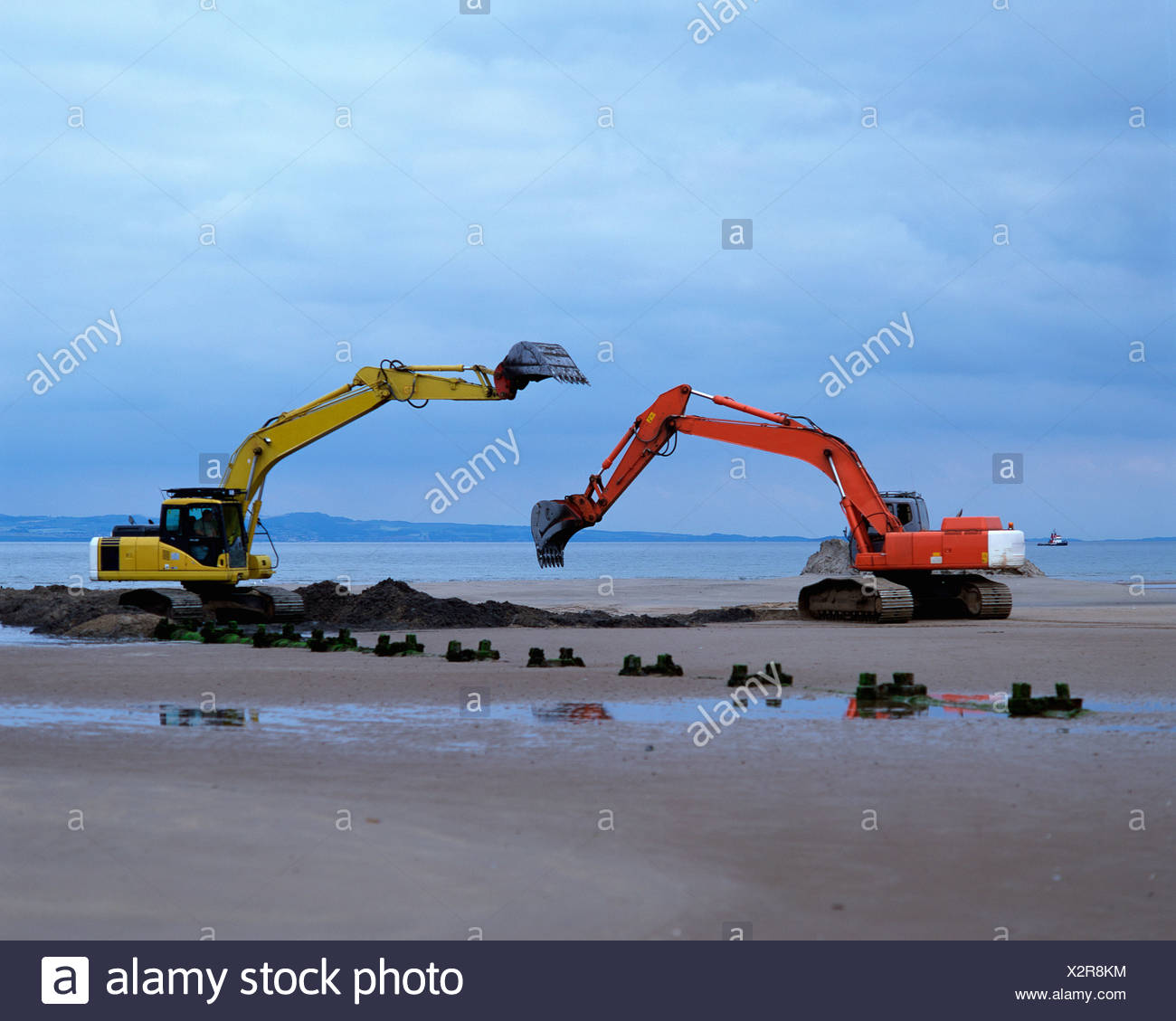Earth movers on beach - Stock Image