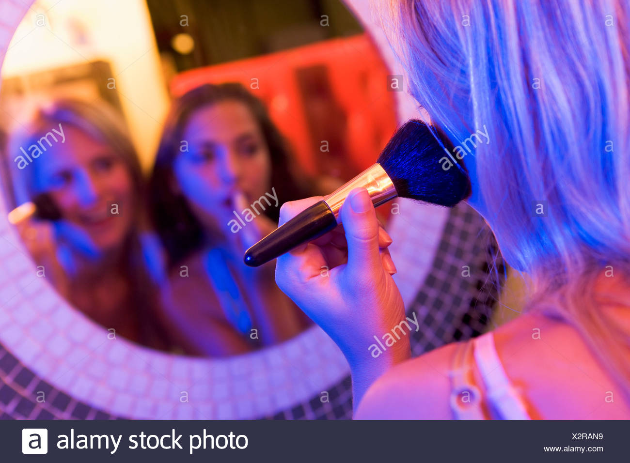 Two young women applying makeup in a mirror - Stock Image