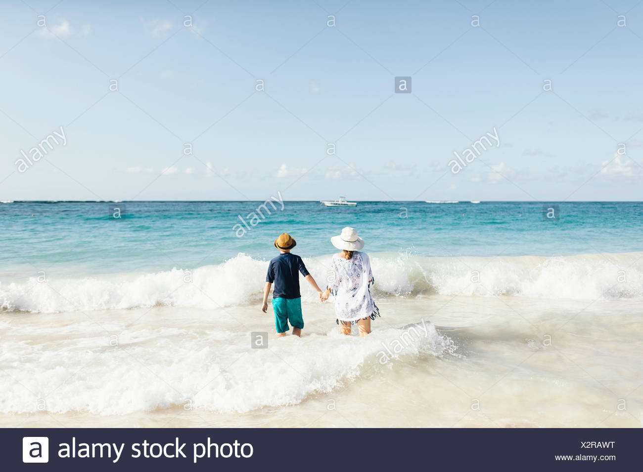 Mother and son, holding hands, standing in surf on beach, rear view - Stock Image