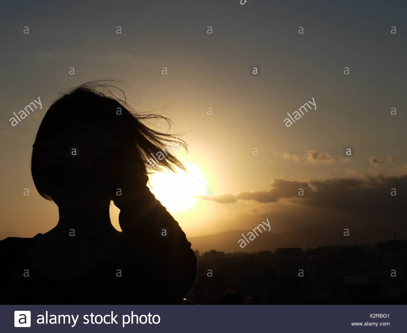 Rear View Of Silhouette Woman Against Sky During Sunset - Stock Image