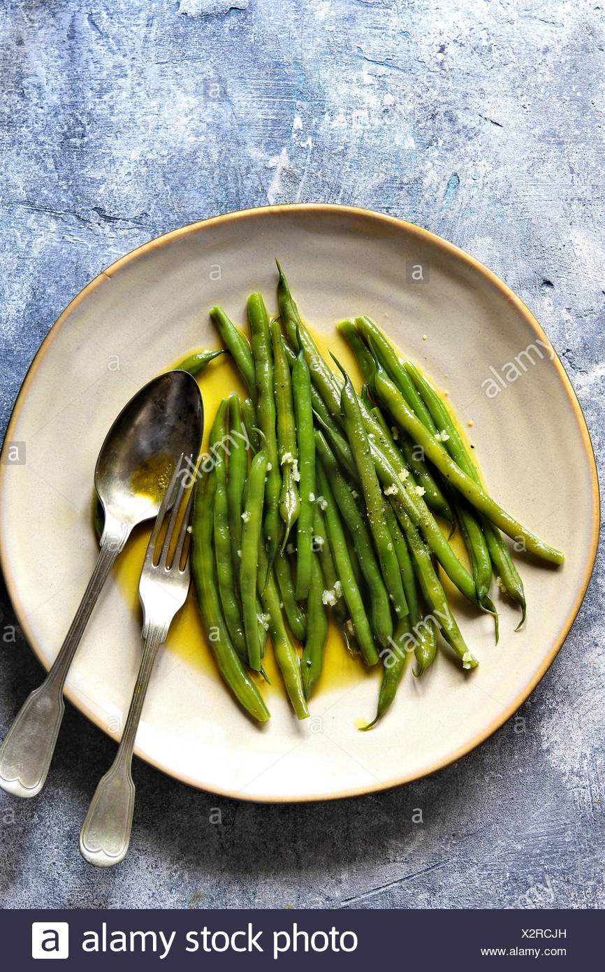 Sauteed green beans with olive oil and garlic on a serving plateTop view - Stock Image