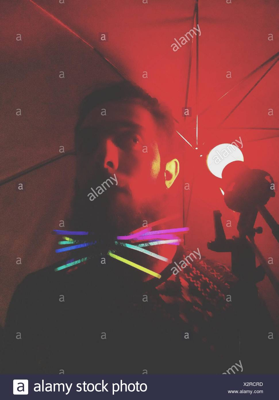 Low Angle View Of Man With Illuminated Colorful Lighting Equipment Standing Under Umbrella - Stock Image
