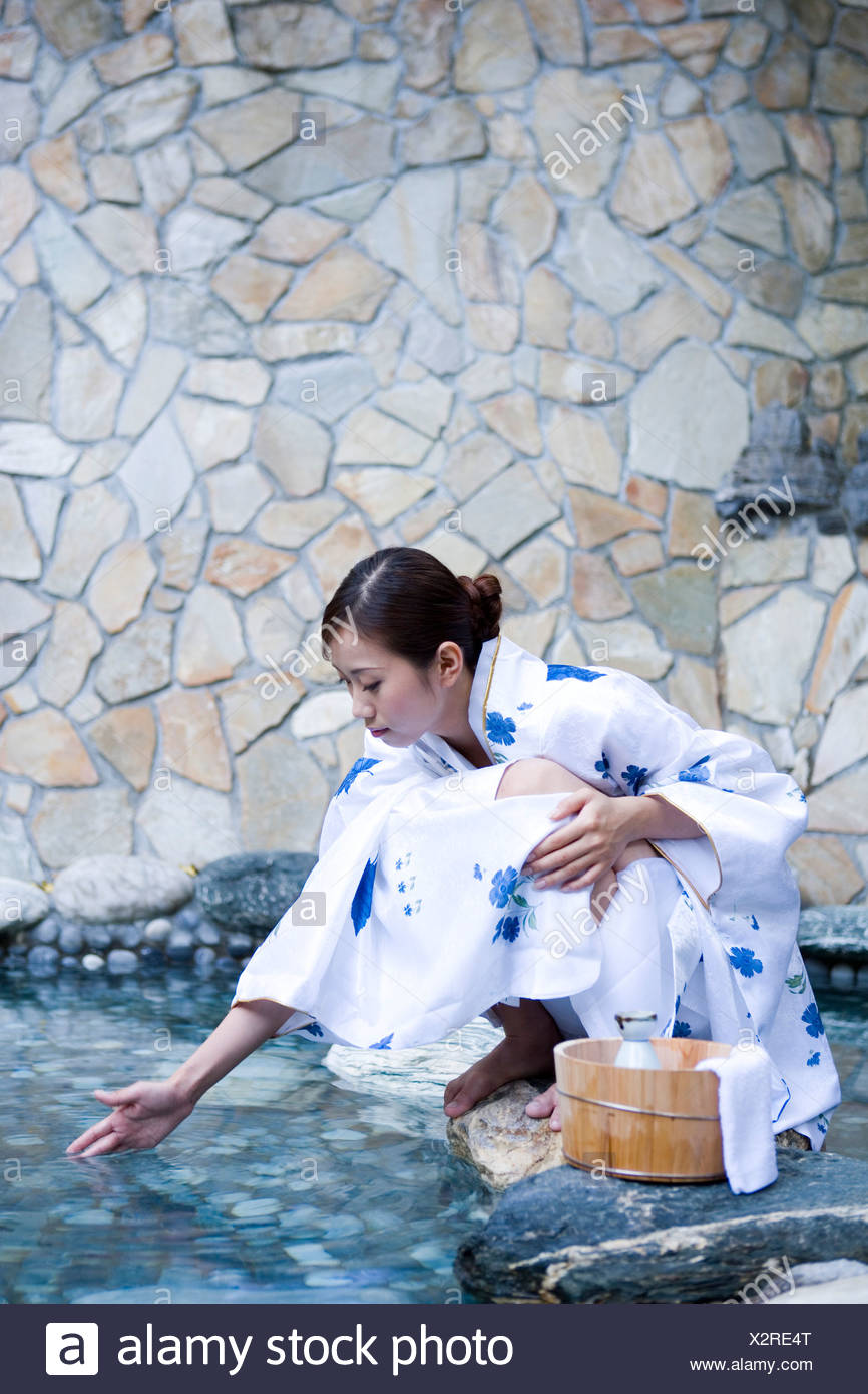 Young woman in kimono crouching by hot spring - Stock Image