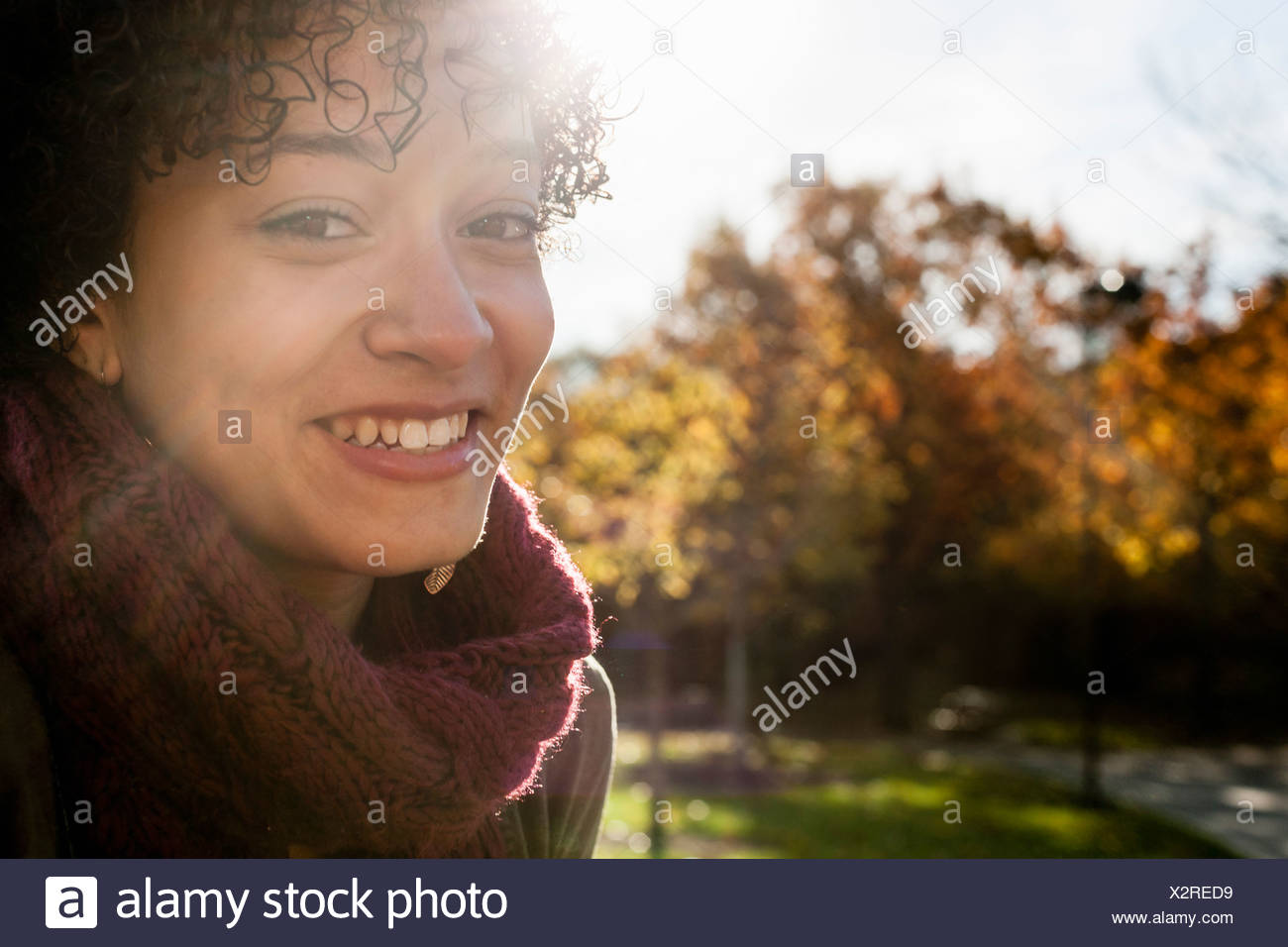Young woman in park on autumn day - Stock Image