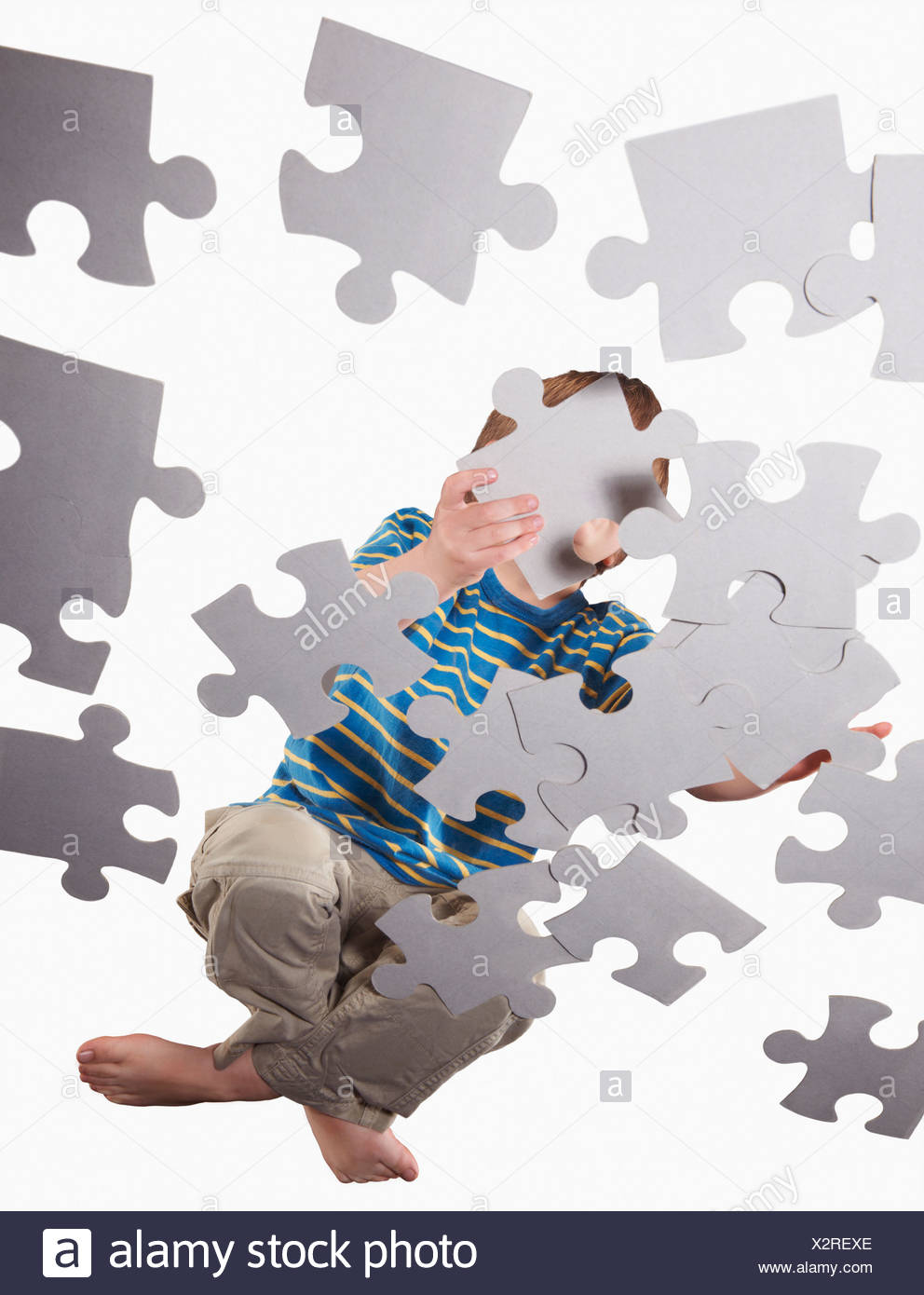 Boy playing with oversize jigsaw puzzle - Stock Image