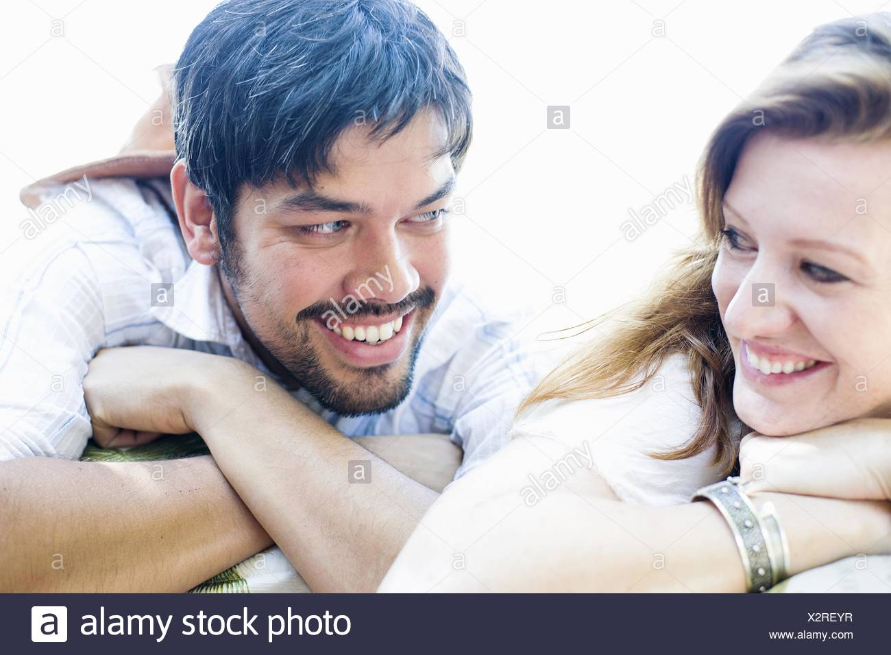 Close up portrait of happy couple making eye contact - Stock Image