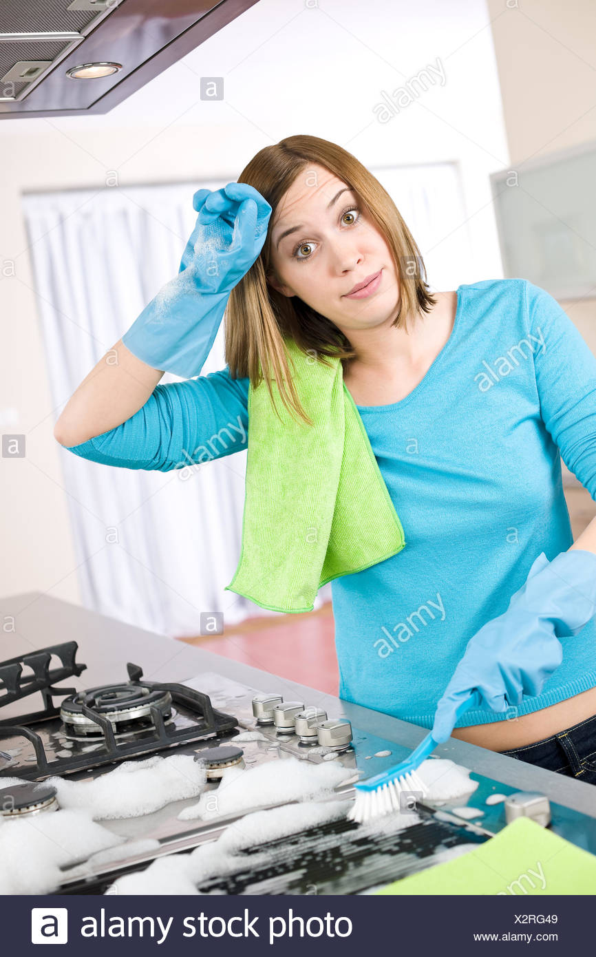 Cleaning - Tired woman cleaning stove in modern kitchen Stock Photo ...