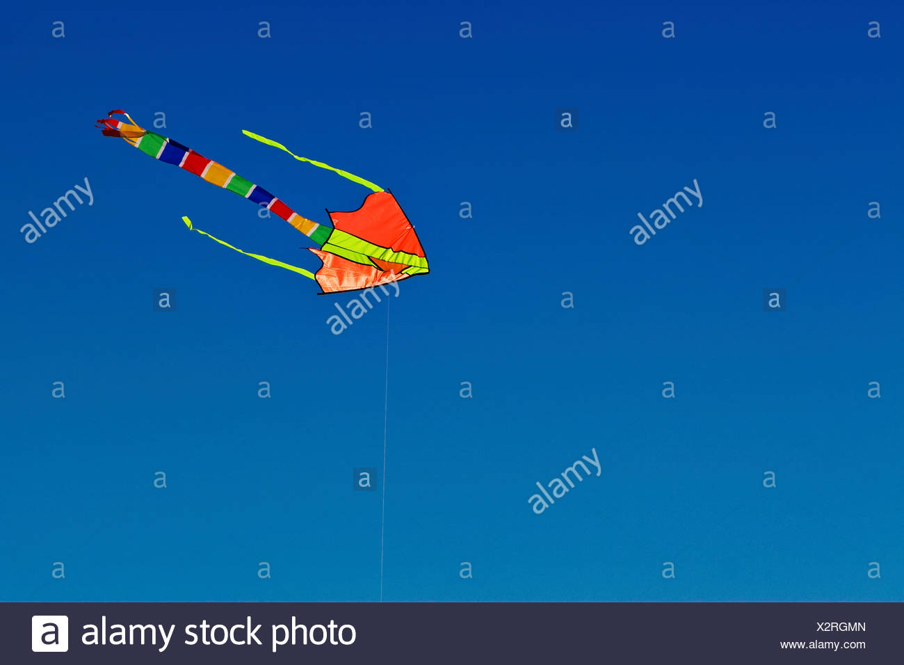 Colorful kite fluttering and flying in blue sky - Stock Image