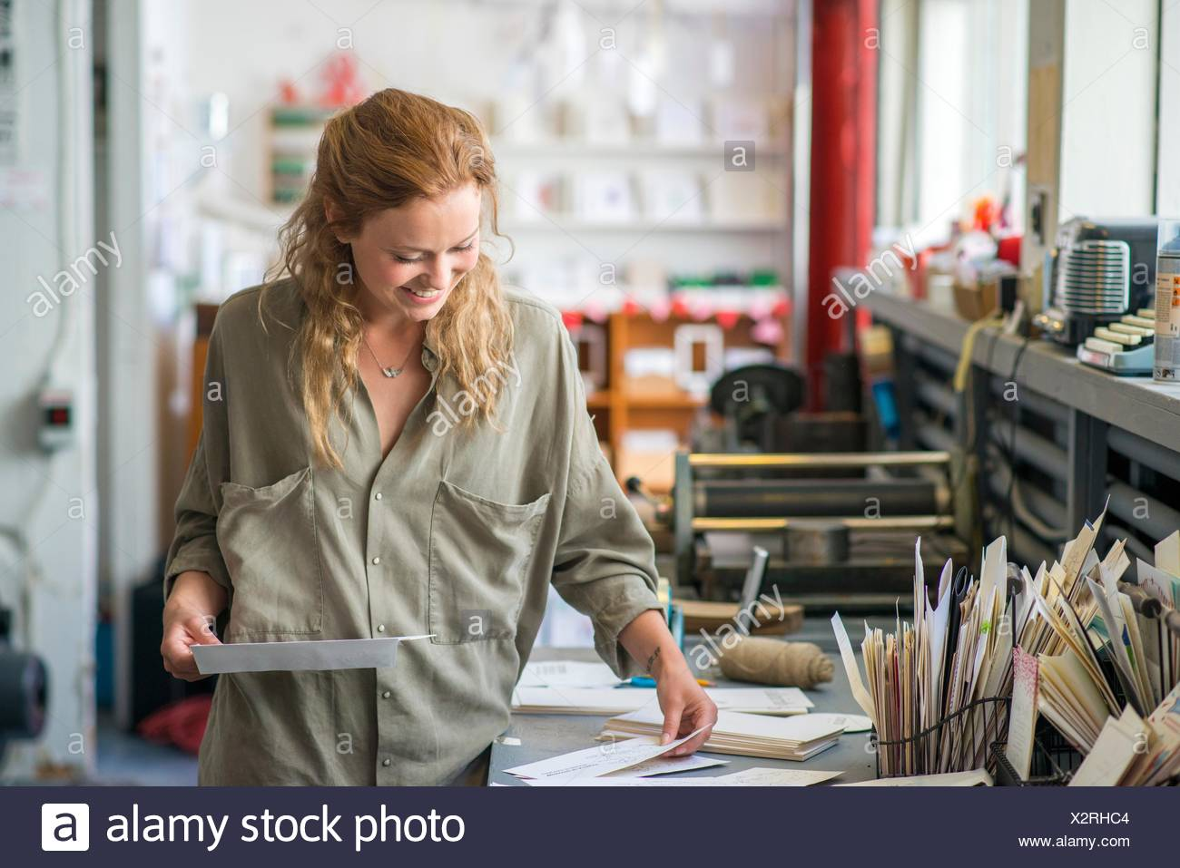 Female print designer examining designs in workshop - Stock Image