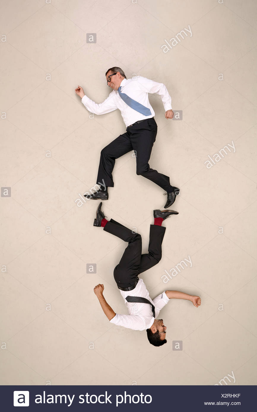 Two symmetric businessmen on the move - Stock Image