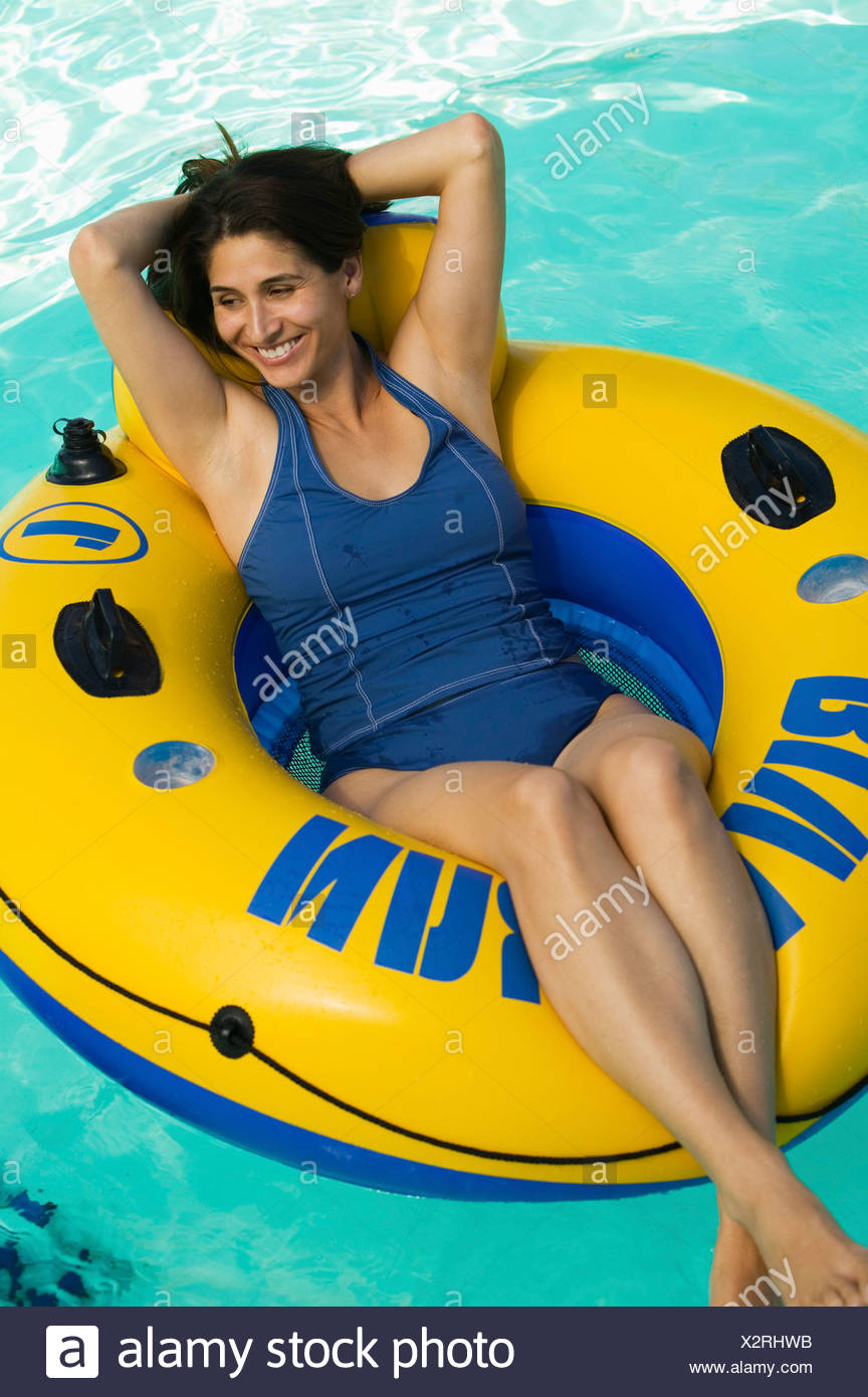 Woman Lying On Inflatable Raft In Swimming Pool Elevated