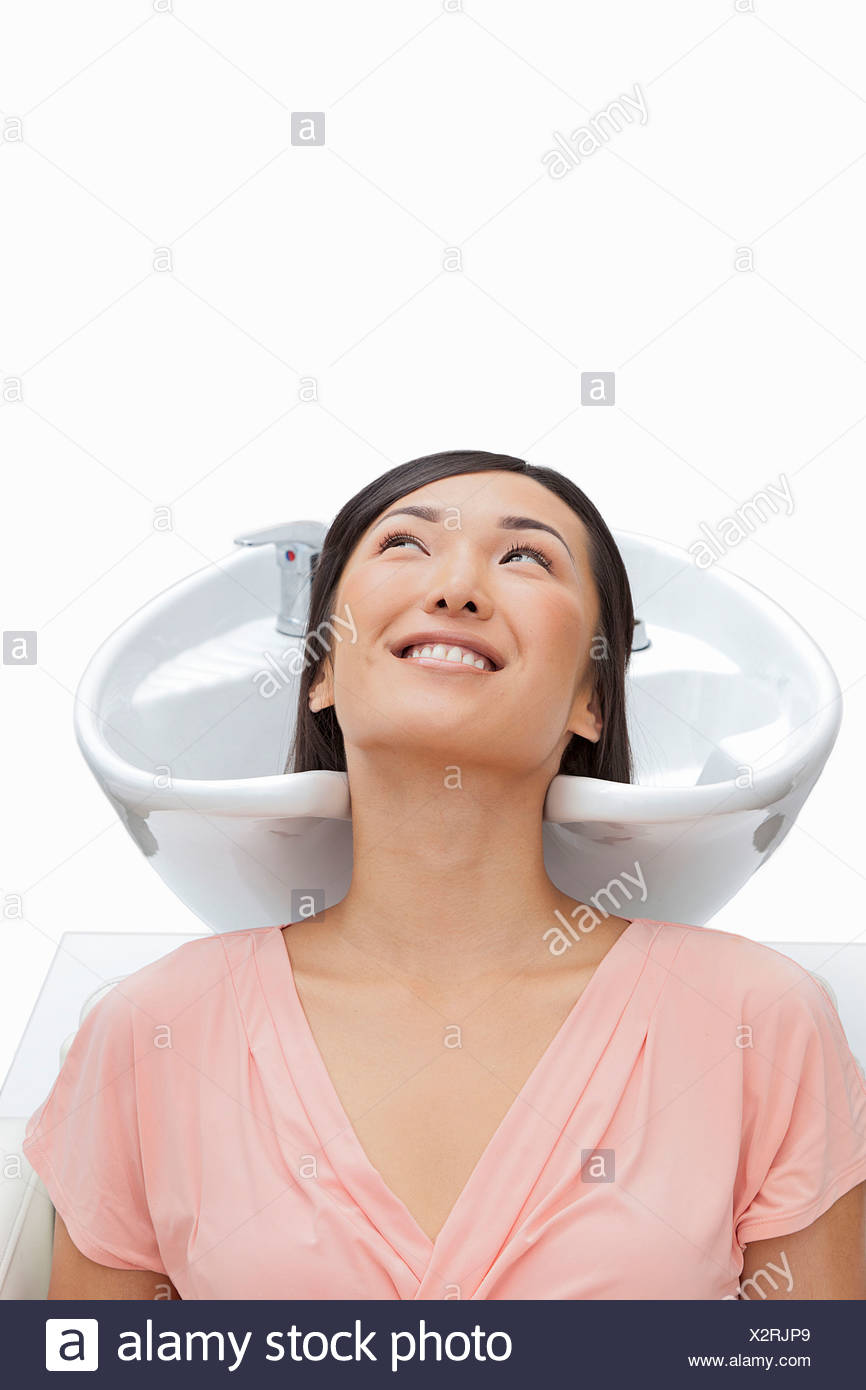 Woman resting head in sink against white background Stock Photo